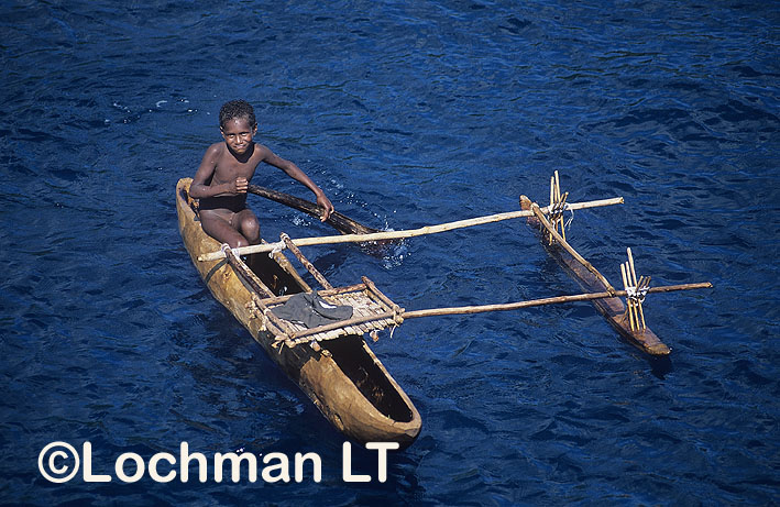 Madang Province –  a boy in a traditional canoe
